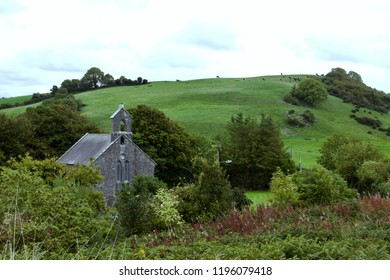 View of Irish countryside with fields, trees, and a church in the landscape