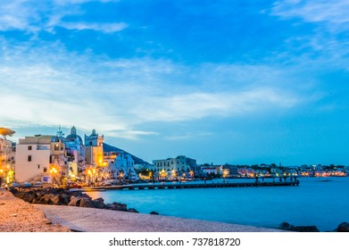 View of Ischia Island, buildings and pier lit at twilight with people in the background enjoying the evening.
