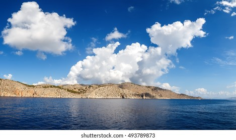 view of the island in Aegean sea, clouds, Sunny summer day