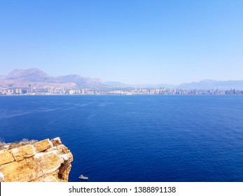 View from the island of Benidorm, Spain. Image of the view from above with all the Mediterranean Sea and the skyline and beaches of Benidorm and low scrub and rock in the foreground.