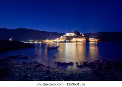 View of the island of Spinalonga with calm sea at night. Here were isolated lepers, humans with the Hansen's desease, gulf of Elounda, Crete, Greece.