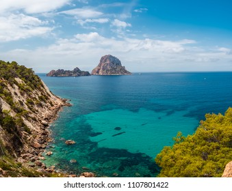 View of the islets of Es Vedrá and Es Vedranell, from the cliff of Cala D'hort, in Ibiza, Spain