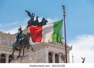 View of Italian national flag in front of Altare della Patria (Altar of the Fatherland) , the equestrian sculpture of Victor Emmanuel and statue of the goddess Victoria riding on quadrigas on top.