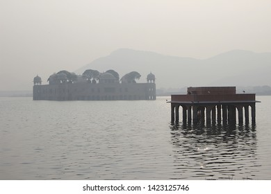 View of Jalmahal Summer Palace at Jaipur on a misty morning with silhouetted stone structure in the foreground, Rajasthan, India, Asia