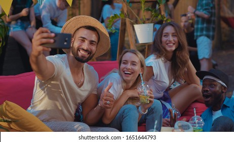 View of joyful drunk young friends making funny stupid faces taking selfie picture on smartphone at the party. Fun and communication concept.