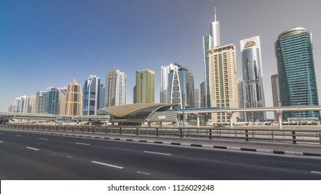 View of Jumeirah lakes towers skyscrapers and metro sration timelapse hyperlapse with traffic on sheikh zayed road and tram line. Sunny day with blue sky