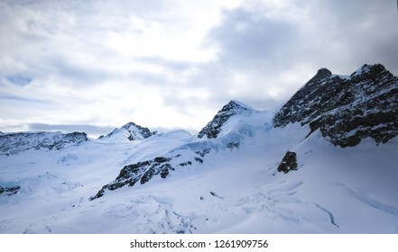 View from Jungfraujoch, top of alps alpine mountain in Switzerland, white snow landscape scenery with coldness before sunset.