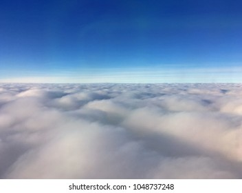 View just above a layer of clouds which blanket far into the distance to the blue horizon
