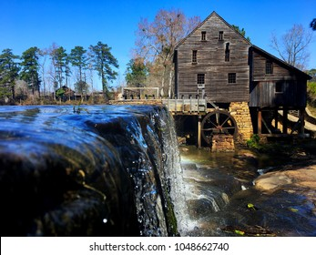 View from just above water level of the waterfall and the old gristmill with its flume and waterwheel at Historic Yates Mill County Park at Raleigh North Carolina, Triangle area, Wake County.