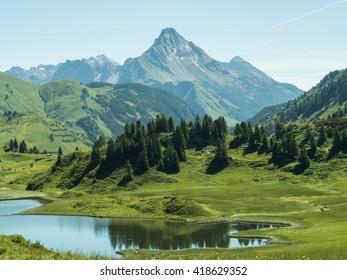 A view of the Kalbelesee lake surrounded by the Alpine mountains near village Schroecken in Bregenzerwald, region Vorarlberg, Austria