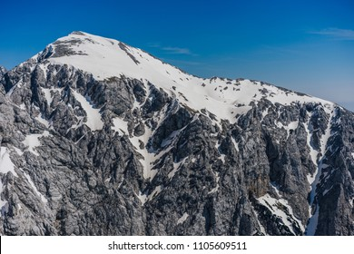 View of Kamnik Savinja alps, Slovenia. Stunning view over mountain alpine landscape with snow, rocks and summit of Brana. Blue sky, dramatic clouds. Background wallpaper photo of mountains.