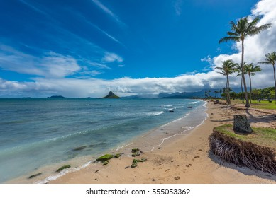 View of Kaneohe Bay, Hawaii with Mokolii, commonly known as Chinaman 's Hat, and beautiful beach with visible reef and waves