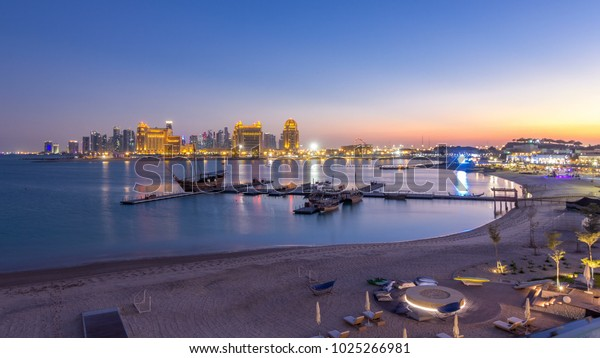 View from Katara Beach day to night transition timelapse after sunset in Doha, Qatar, towards the West Bay and city center. Illuminated skyscrapers. Old ship on foreground