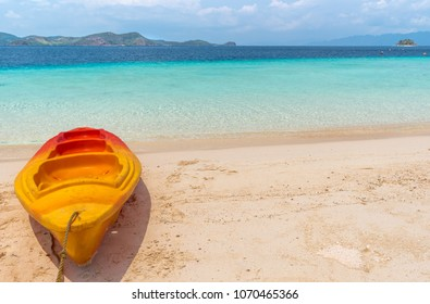 View of kayak on tropical beach on the Banana island, Busuanga, Palawan, Philippines. Beautiful tropical island with sand beach, palm trees. Travel concept