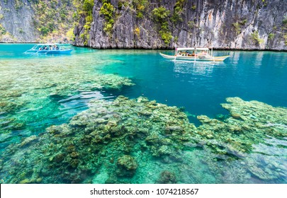 View of Kayangan Lake lagoon with tourists boat and coral reef on Coron island, Busuanga Palawan Philippines