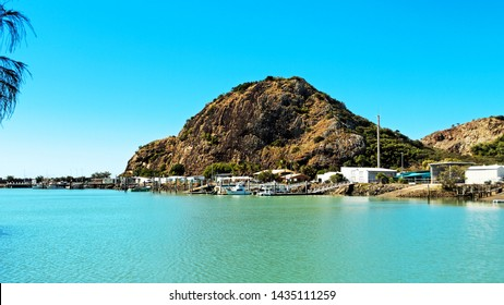 View from Keppel Bay Marina showing the harbour waterfront buildings and its protective mountain with blue sky overhead. The Great Barrier Reef, Queensland, Australia.