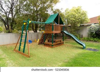 View of kids playground in green backyard garden