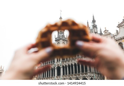 View of the King House or the Museum of the City of Brussels at the Grand Place in Brussels through a hole in the traditional Belgian waffle. Conceptual idea, concept. Travel to Belgium