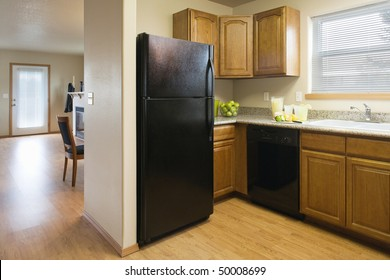 View of a kitchen with a black refrigerator and wood cabinets, showing a partial view of the dining room and living room areas. Horizontal shot.