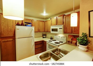View of kitchen cabinets with sink and white old appliances