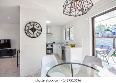 View of the kitchen and dining area featuring beautiful wall and ceiling decor, a glass table and 4 chairs