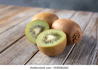 A view of kiwi on a wood table surface, featuring whole fruit and one fruit cut open.