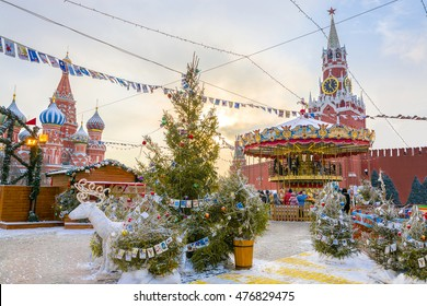 View of Kremlin and Cathedral of St. Basil at the Red Square decorated for New Year and Christmas holidays in winter at sunset, Moscow, Russia.