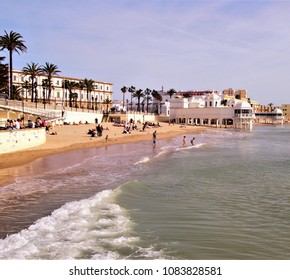 view of La Caleta Beach, Cádiz, Spain, with colonial building and unrecognizable people sunbathing and bathing in the sea,