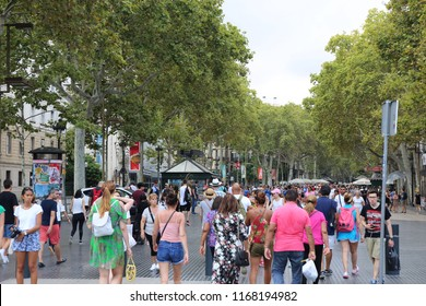 View of La Rambla, a tree-lined pedestrian street, in central Barcelona, Spain, August, 27, 2018. Many people walking in the famous avenue lined with plane trees. Old typical buildings on each side.