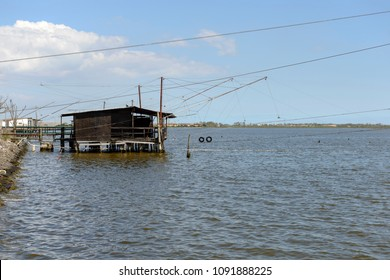 view of  the lagoon briny water with old traditional stilt fishing hut, shot in bright spring sun light at Comacchio, Ferrara,  Italy