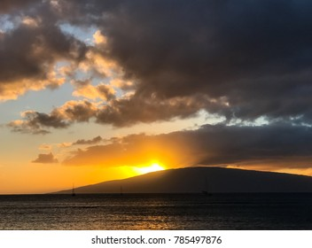 A view from Lahaina, Maui across the water to the sun setting behind the island of Lanai, reflecting on the gray clouds above.