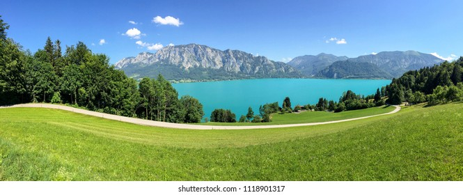 View to lake Attersee with green pasture meadows and Alps mountain range near Nussdorf Salzburg, Austria