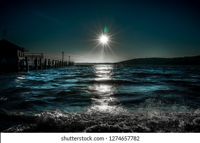 A view of Lake Geneva and the sun setting on the horizon in high aquatic colored contrast, casting silhouettes and shadows in the waves and the pier.