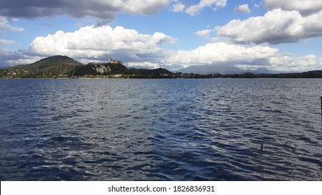 A view of the Lake Maggiore from Arona with a cloudy sky and the Rocca Borromea of Angera on the background. Photo shot with daylight. Arona, Italy.