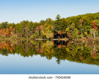 View of a lake, mirror effect of the trees on the water. Norway, New Hampshire, New England, USA.