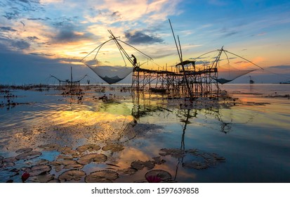 A view of the lake in the morning at Pakpra, Phattalung, Thailand and the fisherman's way of life catching fish using a large net.