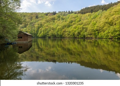 View of Lake Nisramont and boathouse in spring with reflections and fresh foliage on the trees. The lake is formed by a weir in the river Ourthe, the Barrage de Nisramont,  in the Ardennes, Belgium.