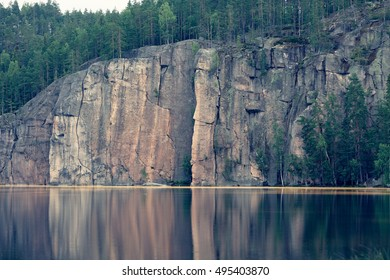 View of lake Olhava in Finland with vertical granite crags going straight from the lake up to 50 meters high