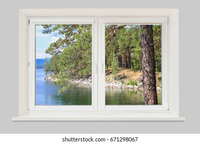 View of the lake and pine forest from the window of the house