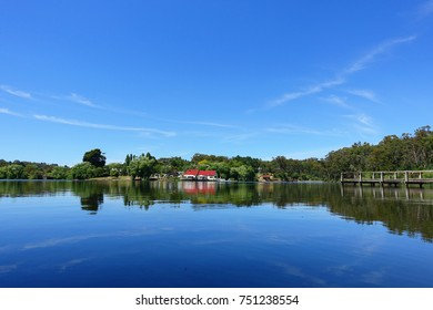 View of a lake with red roof house and wood pier in distant. The clear lake reflecting blue sky in a bright sunny day. Daylesford, Victoria, Australia.