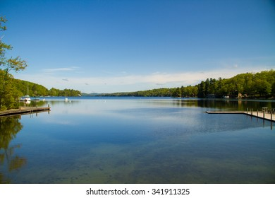 A view of a lake from the shore on a clear day.