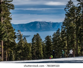 A view of Lake Tahoe from the top of Northstar Ski Resort, in the Sierra Nevada Mountain Range in Truckee, California, with pine trees framing the lake, as skiers ski down the ski slopes.