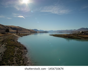View of Lake Tekapo, New Zealand, with turquoise blue water and sun flare
