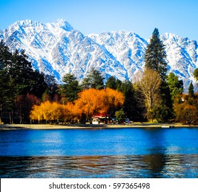 View from Lake Wakatipu of the Remarkables Mountain Range in Queenstown, New Zealand. Taken in Fall with the lake in the foreground, autumnal trees and snowy mountains in the background.