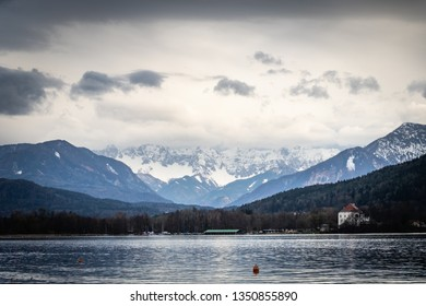 View from lake Woerthersee to mountain range Koschuta on a cloudy spring day in Carinthia, Austria