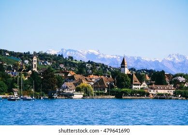View of lake Zurich in summer, with the Swiss Alps in the background.