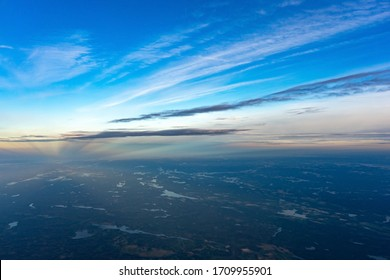 View of the land, fields, and clouds from above.
