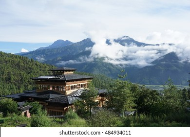 A view of landscape in Paro, Bhutan, overlooking a traditional building and cloud covering mountain's peak on a sunny day.
