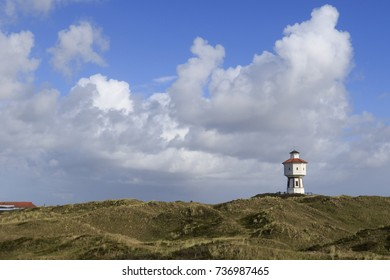 View of Langeoog. East Frisian island belongs to Lower Saxony in Germany. Dune landscape at blue sky with clouds and the water tower.