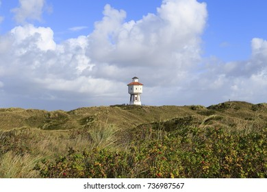 View of Langeoog. East Frisian island belongs to Lower Saxony in Germany. Dune landscape at blue sky with clouds and the water tower in the middle.
